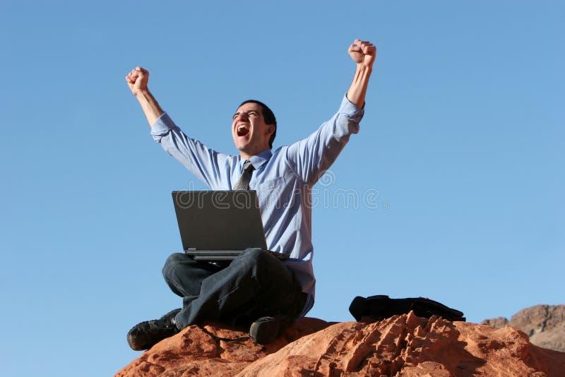 Ecstatic businessman working on laptop