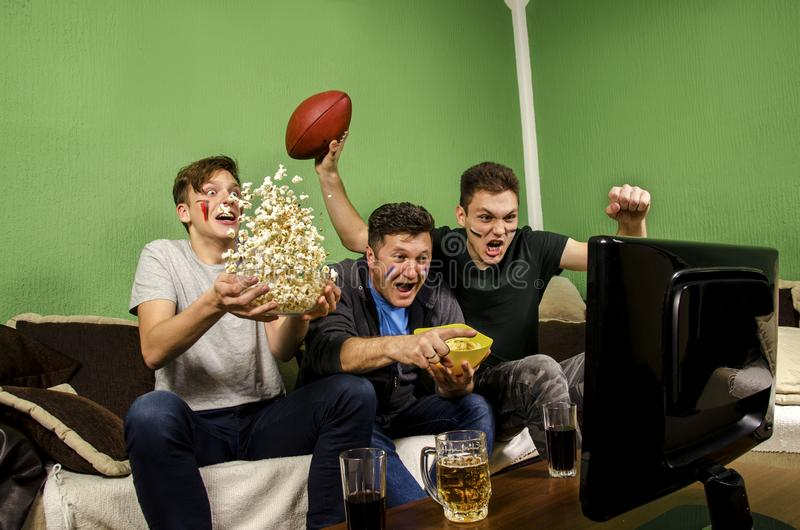 Ecstatic family, father and sons cheering for touchdown royalty free stock images