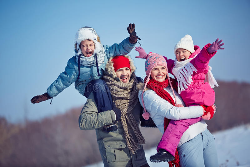 Ecstatic family. Happy family in winterwear having fun outside stock photos