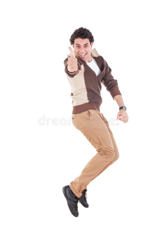 Ecstatic man showing thumbs up jumping of joy and excitement. Ecstatic young casual man showing thumbs up jumping of joy and excitement, Successful proud modern stock photography