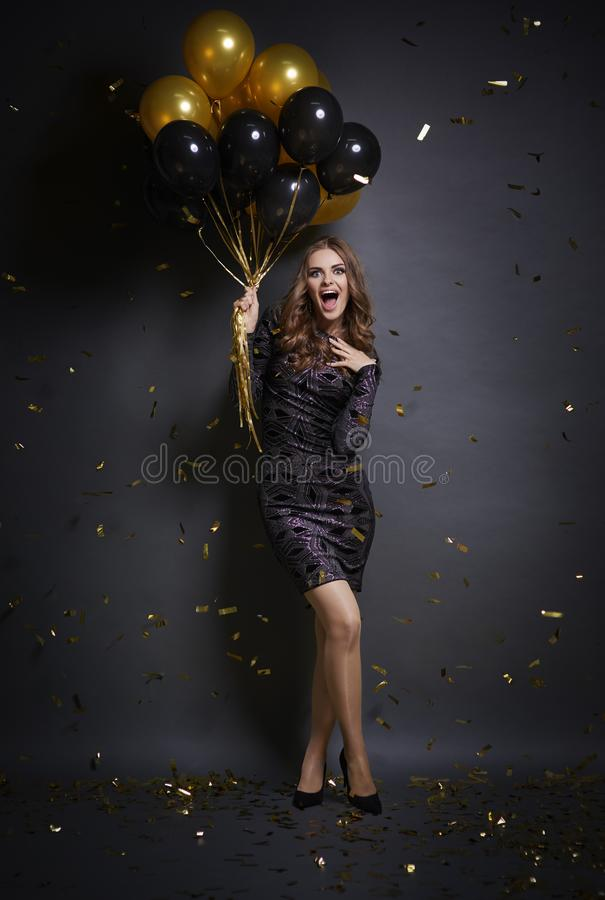 Woman celebrating New Year`s Eve. Ecstatic woman with ballons at studio shot royalty free stock photo