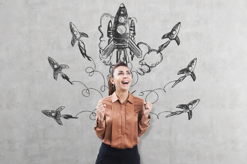 Ecstatic woman near a startup sketch on concrete. Ecstatic woman in a brown blouse is standing near a concrete wall with a startup sketch drawn on it royalty free stock images