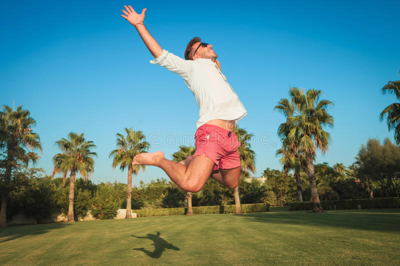Ecstatic young casual man jumping of joy outside stock image