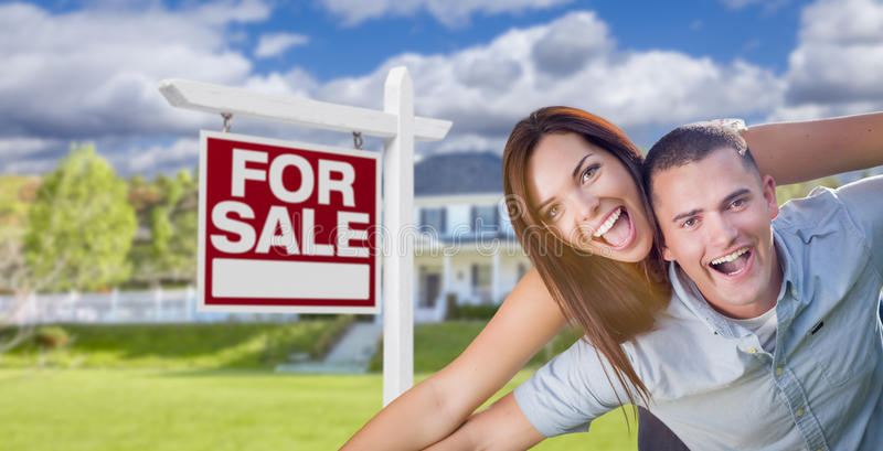 Ecstatic Young Military Couple In Front of Home with For Sale Sign stock image