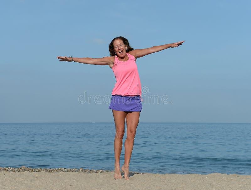 Ecstatically gelukkige vrouw op strand stock afbeeldingen