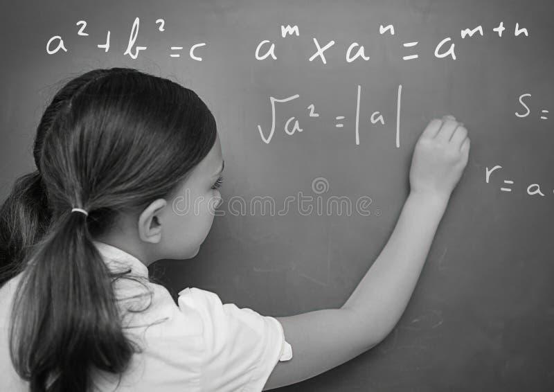Ecuaciones de la matemáticas de la escritura de la muchacha en la pizarra imágenes de archivo libres de regalías