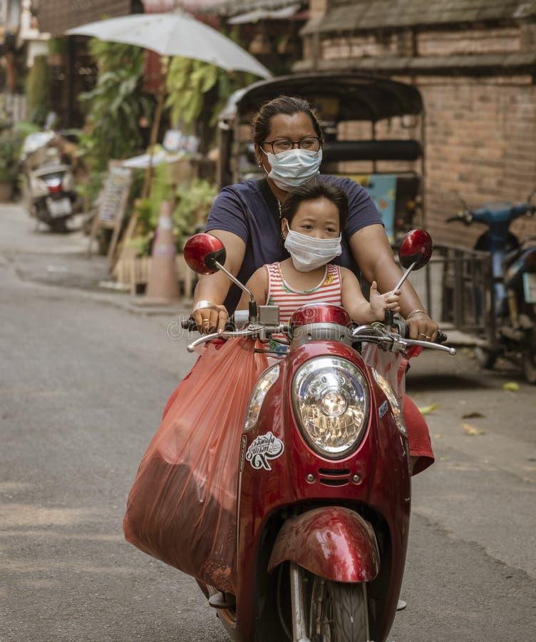 Ed-Bankgok, Tailandia - 2019-30-13 - motociclo di giro della figlia e della madre con le maschere di protezione immagini stock libere da diritti