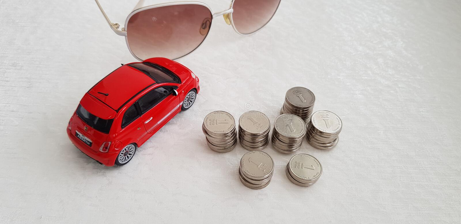Ed fiat 500 abarth toy on white table near sunglasses and pile of Israeli shekel coins royalty free stock image
