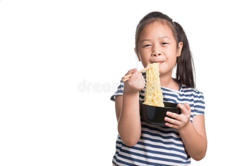 Edad asiática de la muchacha del niño 7 años, comiendo los tallarines inmediatos en b blanco fotografía de archivo