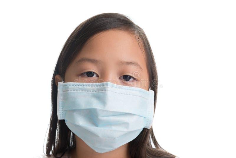 Edad asiática de la muchacha del niño 7 años con la máscara de la protección contra viru de la gripe imagenes de archivo