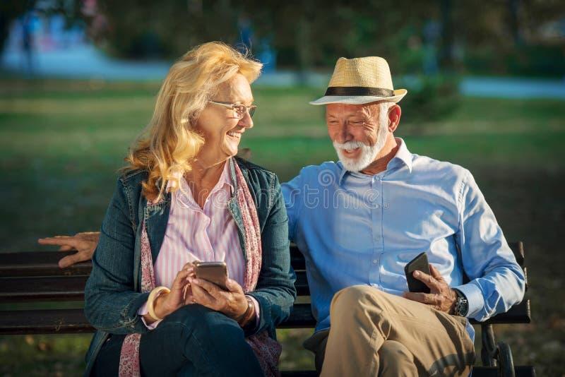 Edad avanzada, tecnología y concepto de la gente - los pares mayores felices con smartphones en el verano parquean foto de archivo