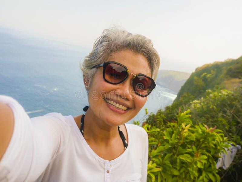 Edad Media mujer asiática feliz y alegre de 50s con el pelo gris que toma el selfie con el teléfono móvil en la isla tropical her fotos de archivo libres de regalías