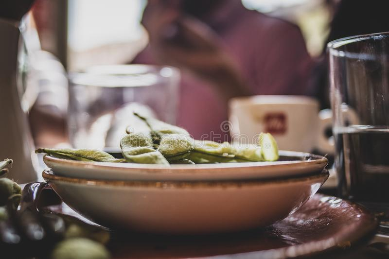 Edamame on clay plates at a cafe. Healthy food edamame on clay plates at s rustic cafe with bokeh of food in the background royalty free stock photography