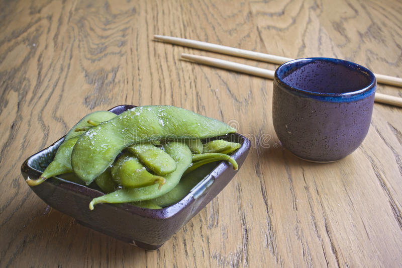 Edamame com chopstiks do vidro e do sushi da causa imagem de stock royalty free