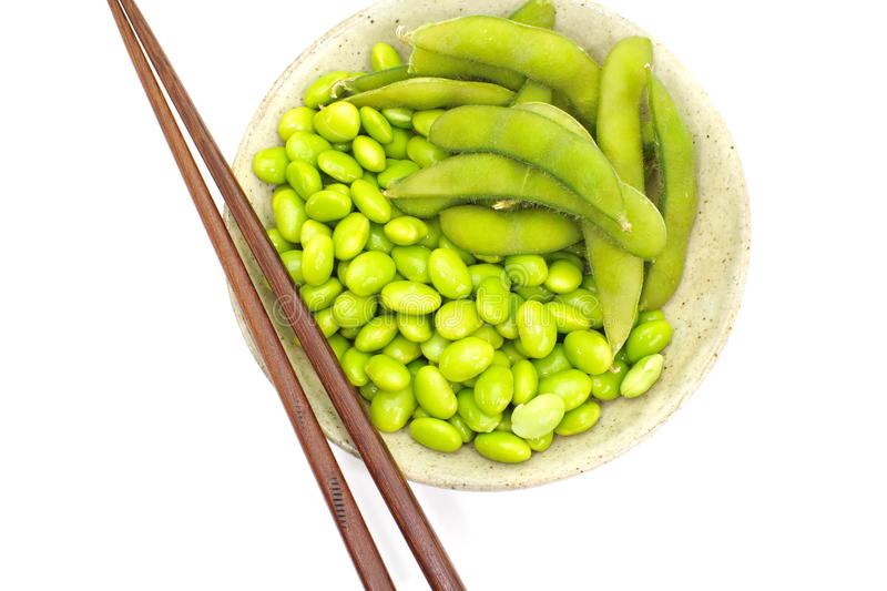 Edamame nibbles, boiled green soy beans, japanese food. Isolated on white royalty free stock image