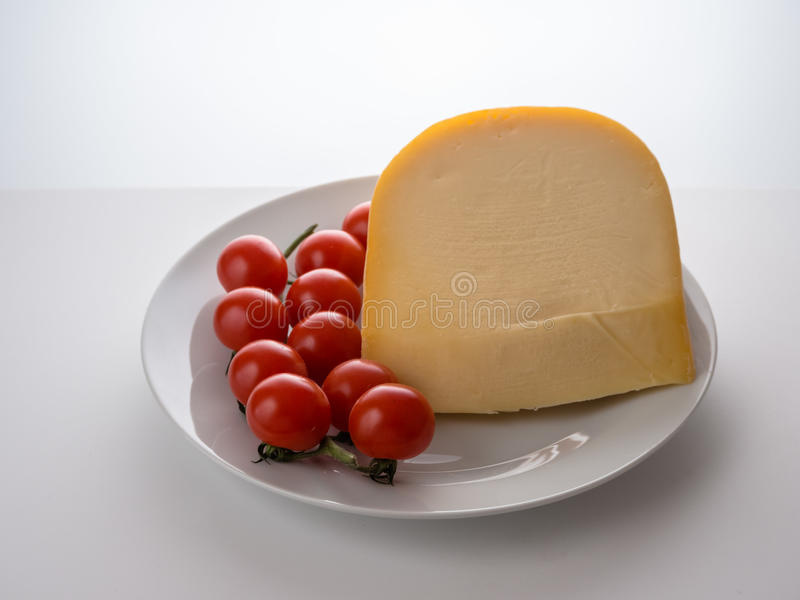 Edammer kaas en kleine tomaten stock foto