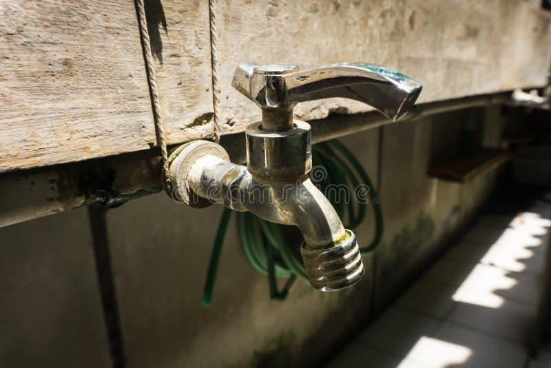 Edelstahlhahn mit Wasserleitungslinie auf einer Backsteinmauer Foto eingelassenes Duri Tangerang Indonesien lizenzfreies stockbild