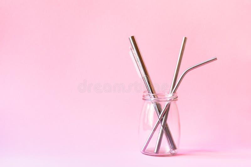 Edelstahlstrohe und Reinigungsbürste in der Glasflasche auf rosa Hintergrund, eco freundlicher Lebensstil, Kopienraum stockbild
