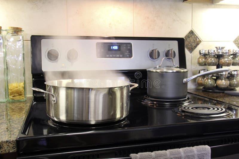 Edelstahltöpfe, die auf Küchenofen kochen lizenzfreie stockfotografie