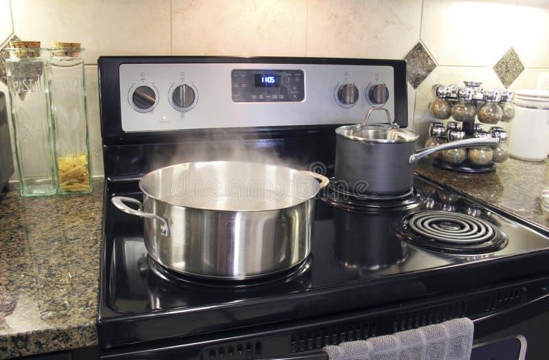 Edelstahltöpfe, die auf Küchenofen kochen stockfotos