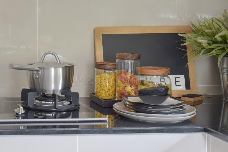 Edelstahltopf- und -teigwarengläser auf schwarzem Granit übersteigen entgegengesetzt lizenzfreie stockbilder