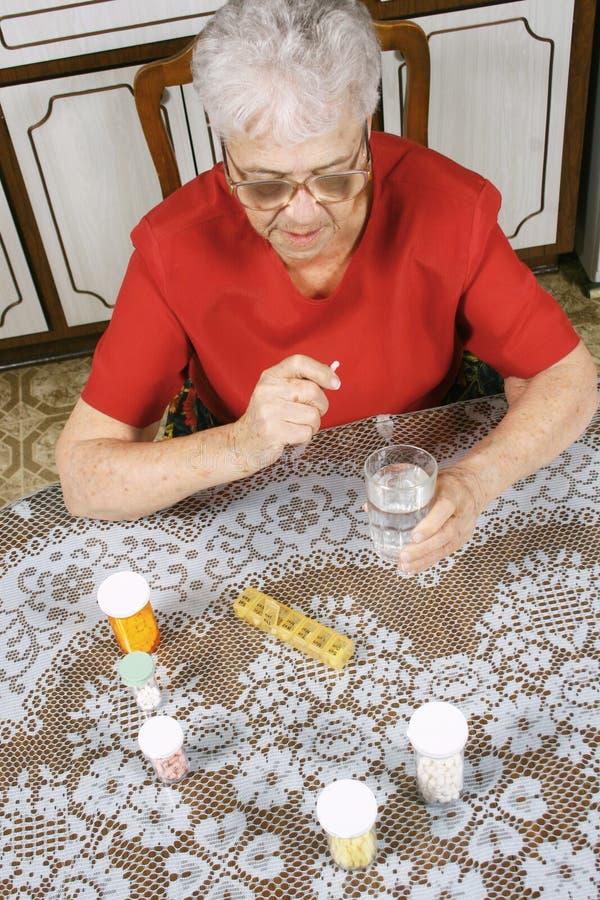 Ederly Frau, die Pillen nimmt lizenzfreie stockfotografie