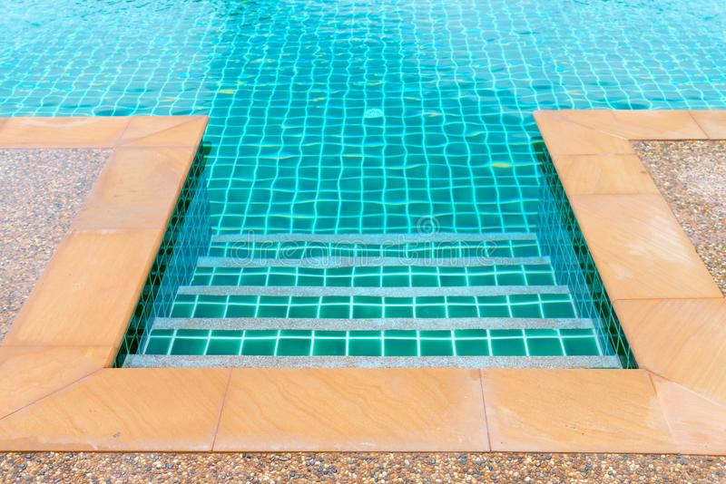 Edge of clean blue swimming pool. With stairs on entry stock photography