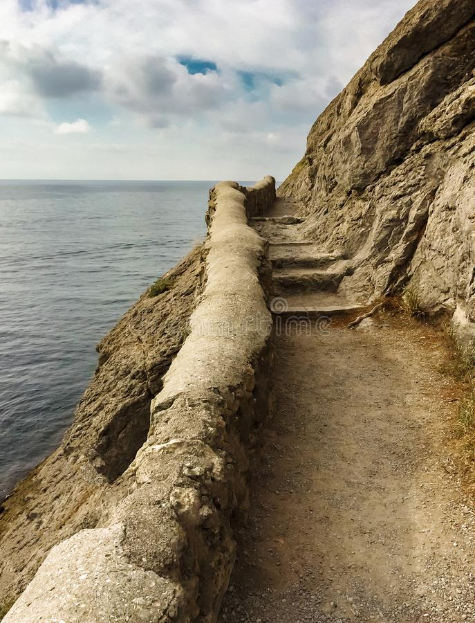 Edge of the cliff with an ancient stone path along the sea with stone steps against the sea and clouds, vertical frame stock photo