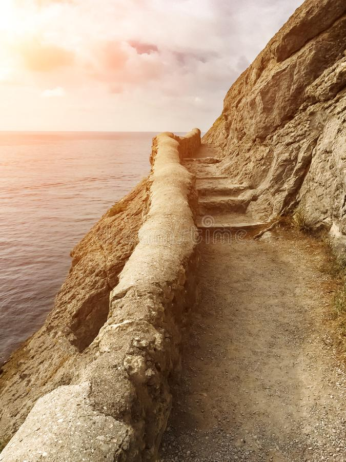 Edge of the cliff with an ancient stone path along the sea with stone steps against the sea with the setting sun, vertical frame royalty free stock photo