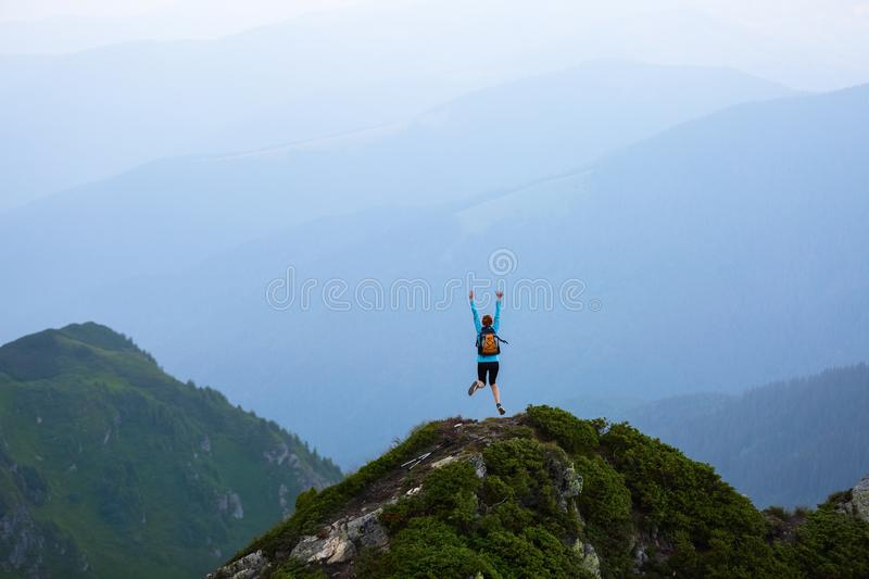 At the edge of the cliff there is a small lawn with the rocks. The tourist girl jumps full of happiness. The high mountains. royalty free stock images