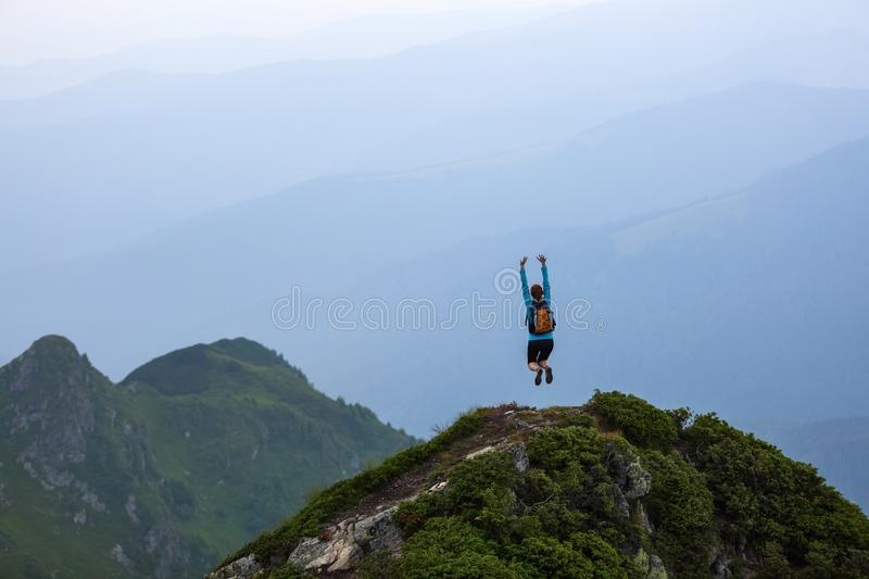 At the edge of the cliff there is a small lawn with the rocks. The tourist girl jumps full of happiness. The high mountains. royalty free stock image