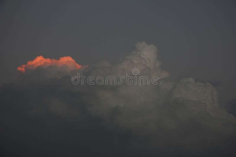 Edge of dark storm cloud is illuminated by ray of sunset sun. Hope concept royalty free stock photography