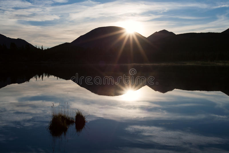 The edge of the rising sun over the mountain and reflection in the lake. Oimyakon Highlands. Yakutia. Russia stock photos