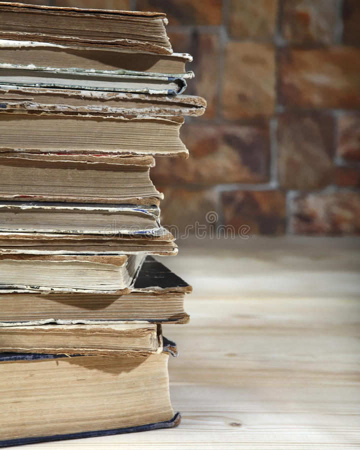 The edge of a stack of old books recumbent on a wooden table. Close-up.  stock photos