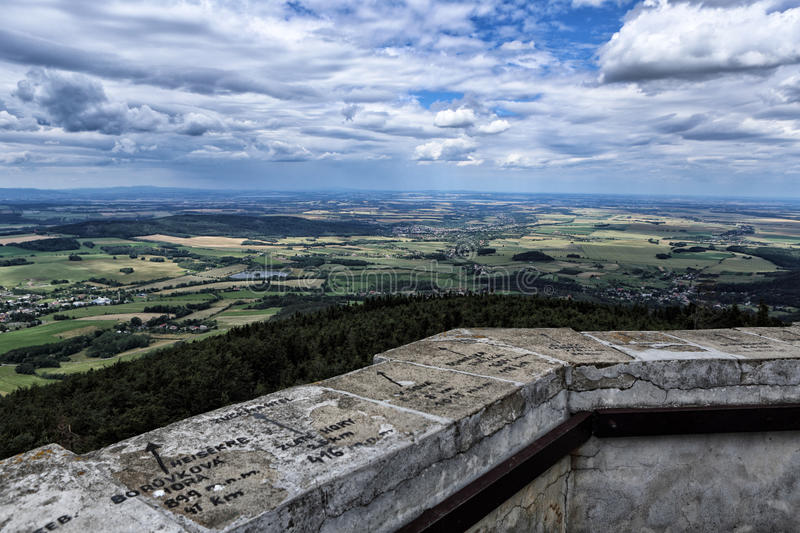 Edge wall of outlook tower with signs and arrows. Edge of stony outlook tower with field and forest scenery royalty free stock photos