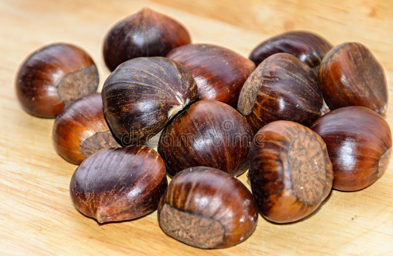 Edible brown chestnuts close up, wooden background royalty free stock photography