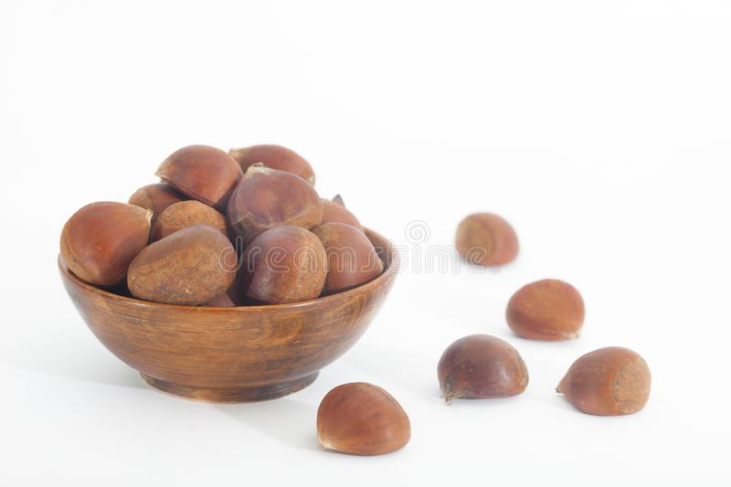 Edible chestnuts in wooden bowl on white background royalty free stock photos