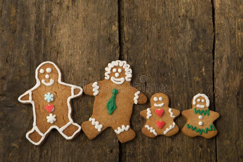 Edible gingerbread family with children. On a rustic wooden board royalty free stock images