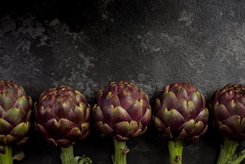 Edible plant, purple artichoke on dark marble background stock photo