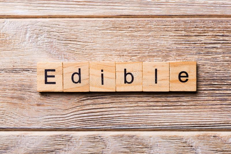 EDIBLE word written on wood block. EDIBLE text on wooden table for your desing, concept stock photography