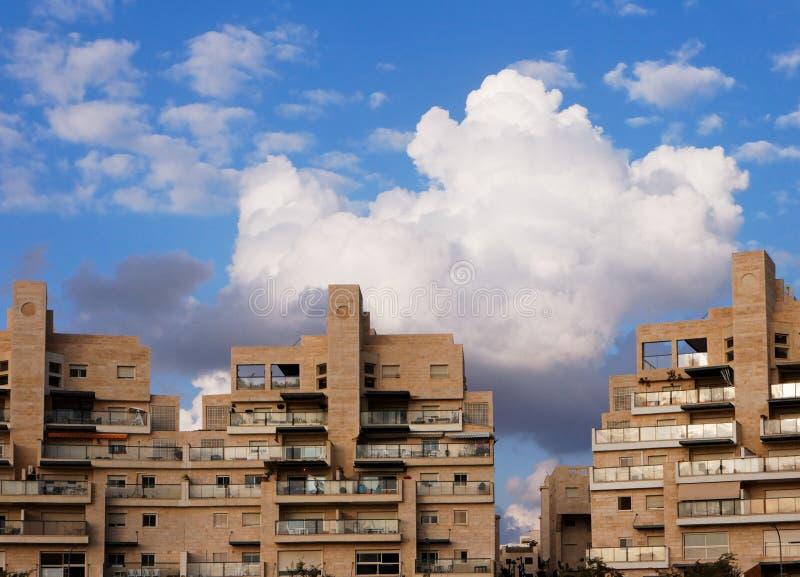 Edifícios e nuvens de apartamento acima dele   imagem de stock royalty free