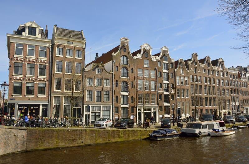 Edifici residenziali storici con i negozi commerciali sul pianterreno sull'angolo del canale di Prinsengracht e del ponte di Rees immagini stock