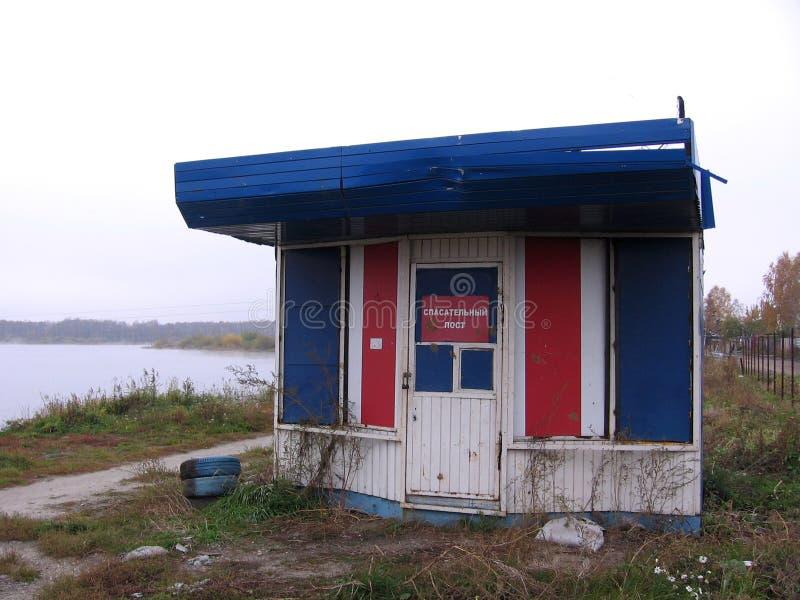 Edificio abandonado quebrado viejo del poste del rescate en la orilla de la charca en el otoño foto de archivo libre de regalías