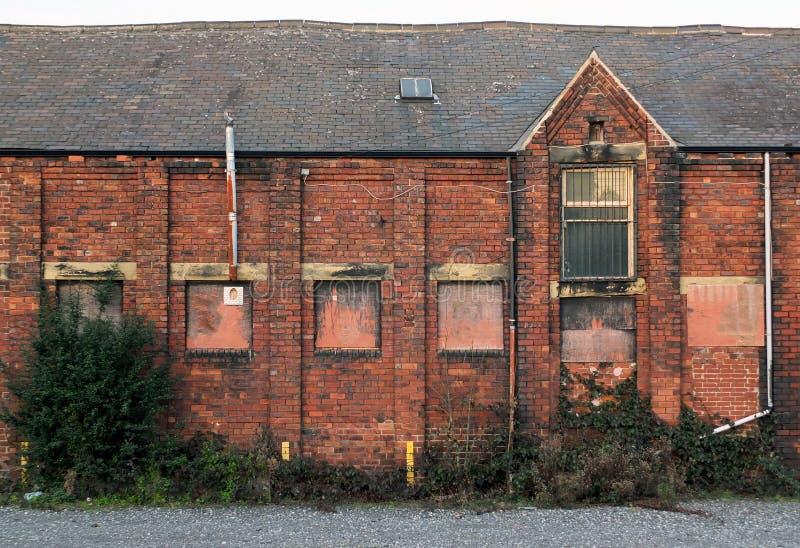 Edificio abandonado viejo de la f?brica del ladrillo con las ventanas ascendentes subidas y las paredes de decaimiento que desmen fotos de archivo libres de regalías