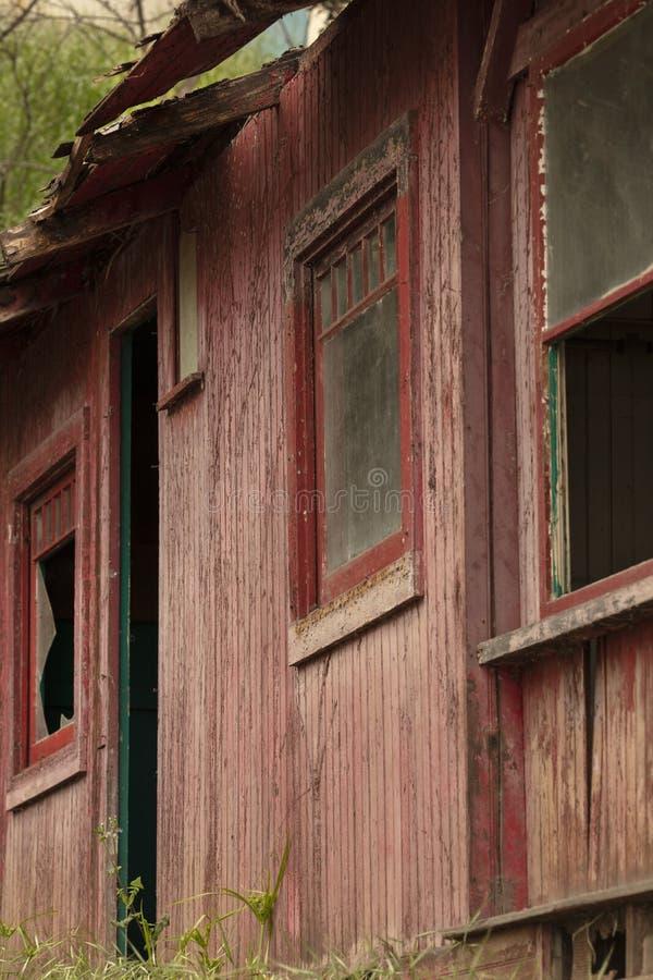 Edificio abandonado viejo que se deshace con las ventanas y las puertas quebradas foto de archivo