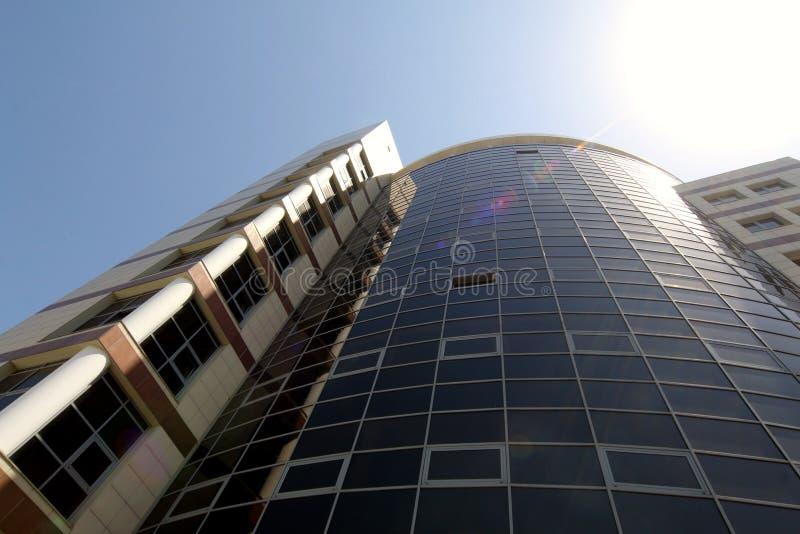 edificio alto comercial en los puntos culminantes del sol en la ciudad fotografía de archivo libre de regalías