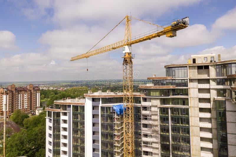 Edificio alto del apartamento o de la oficina bajo construcción Paredes de ladrillo, ventanas de vidrio, andamio y pilares concre imagen de archivo