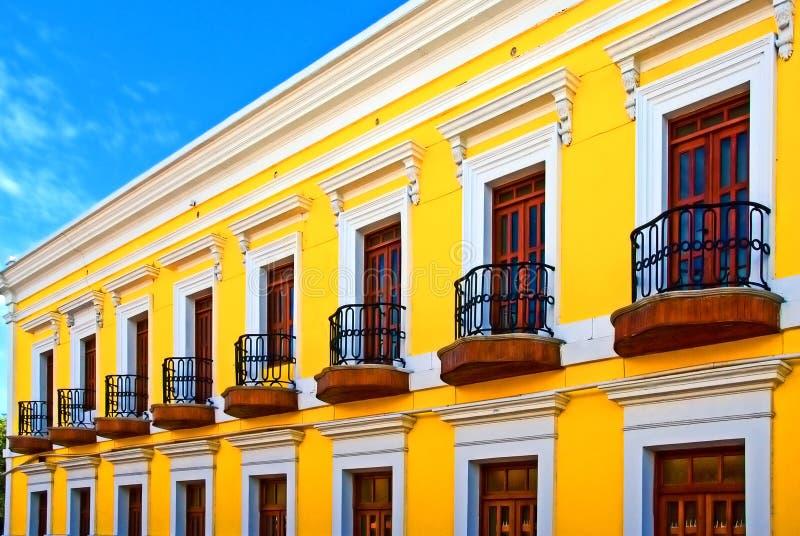 Edificio amarillo brillante del color con los patios imagenes de archivo