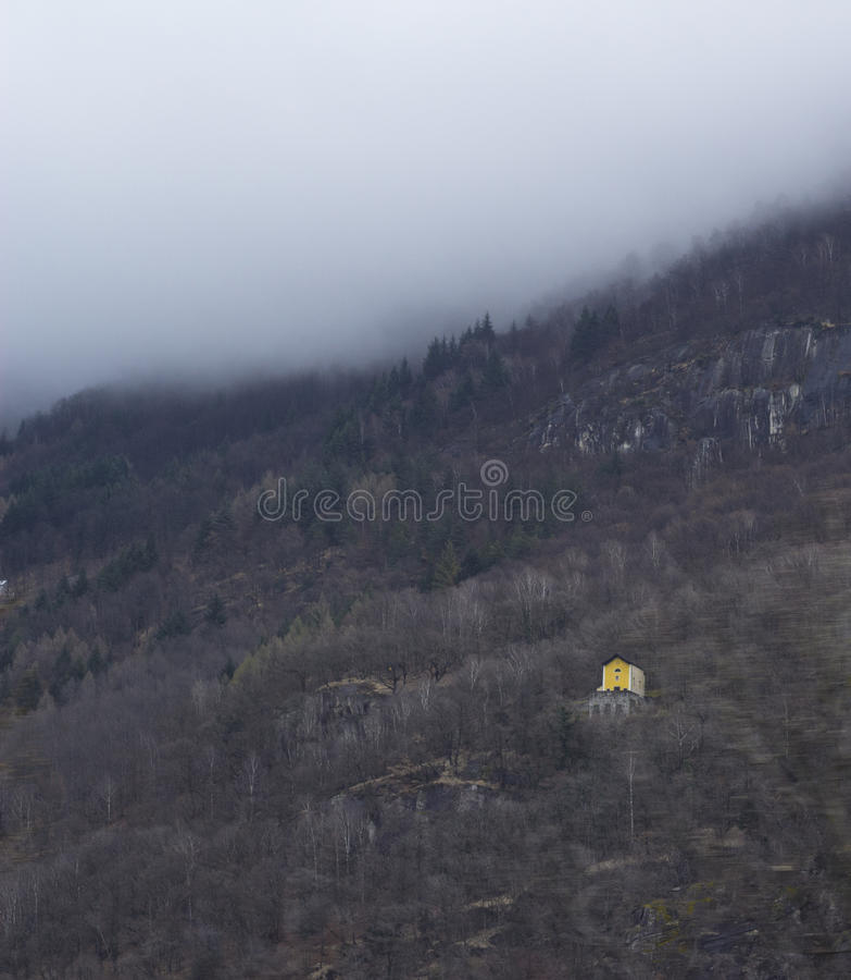 edificio amarillo en la montaña suiza de niebla imágenes de archivo libres de regalías