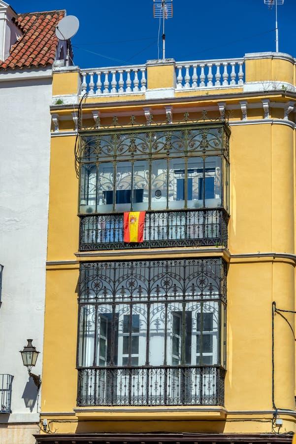 Edificio amarillo y bandera española fotografía de archivo libre de regalías